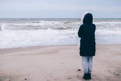 Mujer en abajo la chaqueta que mira el océano Imagen de archivo