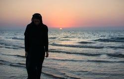 Mujer en abaya en la playa en la puesta del sol Fotos de archivo