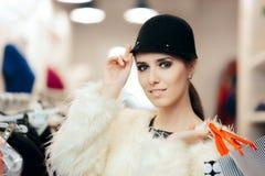 Mujer en abrigo de pieles y compras elegantes lindas del sombrero Foto de archivo