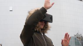 Mujer en abrigo esquimal usando la visión imaginaria del panel en el dispositivo de VR al aire libre Concepto aumentado de la rea metrajes