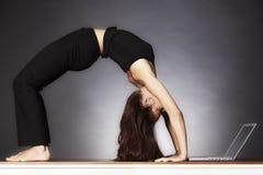 Mujer en actitud de la rueda de la yoga con la computadora portátil. Fotos de archivo libres de regalías