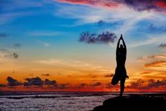 Mujer en actitud de la yoga en roca de la playa del mar Imagen de archivo