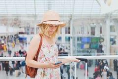 Mujer en aeropuerto que comprueba el teléfono móvil, smartphone app del viajero fotografía de archivo