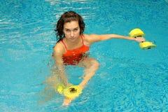 Mujer en agua con los dumbbels Imagen de archivo