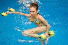 Mujer en agua con pesas de gimnasia Fotos de archivo