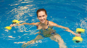 Mujer en agua con pesas de gimnasia Imagen de archivo