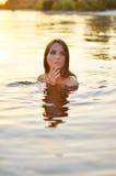 Mujer en agua durante puesta del sol fotos de archivo