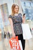 Mujer en alameda de compras usando el teléfono móvil Foto de archivo libre de regalías