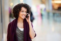 Mujer en alameda de compras usando el teléfono móvil