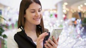 Mujer en alameda usando el móvil que recibe enhorabuena en Año Nuevo Decoraciones de la Navidad en fondo almacen de video