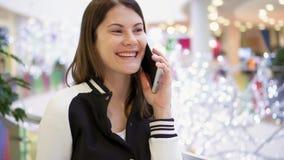 Mujer en alameda usando el móvil que recibe enhorabuena en Año Nuevo Decoraciones de la Navidad en fondo metrajes