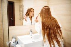 Mujer en albornoz contra el espejo en cuarto de baño fotografía de archivo