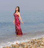 Mujer en alineada rosada en la playa del mar Foto de archivo