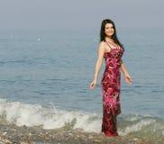 Mujer en alineada rosada en la playa del mar Fotos de archivo