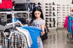 Mujer en almacén de ropa Foto de archivo