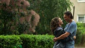 Mujer en amor con su novio que se besa en la lluvia Morenita atractiva y hombre hermoso en ropa mojada que pasan tiempo metrajes