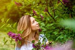Mujer en arbusto de lila floreciente en el día de verano soleado imagenes de archivo