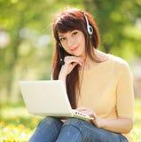 Mujer en auriculares con el ordenador portátil blanco en el parque Imagenes de archivo