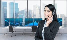 Mujer en auriculares delante de las pantallas con datos comerciales Imagen de archivo libre de regalías
