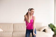 Mujer en auriculares que canta y que baila en casa Imagen de archivo libre de regalías