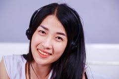 Mujer en auriculares que escucha la música Imágenes de archivo libres de regalías