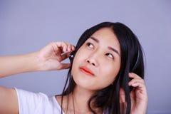 Mujer en auriculares que escucha la música Foto de archivo