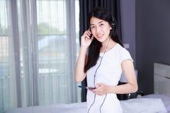 Mujer en auriculares que escucha la música del smartphone en bedroo Foto de archivo