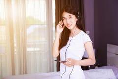 Mujer en auriculares que escucha la música del smartphone en bedroo Imagenes de archivo