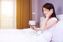 Mujer en auriculares que escucha la música del smartphone en cama adentro Imagen de archivo libre de regalías