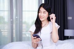 Mujer en auriculares que escucha la música del smartphone en cama adentro Fotografía de archivo libre de regalías