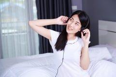 Mujer en auriculares que escucha la música del smartphone en cama adentro Imagen de archivo