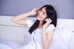 Mujer en auriculares que escucha la música del smartphone en cama adentro Fotos de archivo