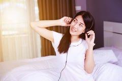 Mujer en auriculares que escucha la música del smartphone en cama adentro Imagenes de archivo