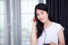 Mujer en auriculares que escucha la música del smartphone con el viento Fotografía de archivo