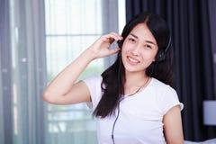 Mujer en auriculares que escucha la música del smartphone con el viento Imagen de archivo