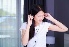 Mujer en auriculares que escucha la música del smartphone con el viento Fotografía de archivo libre de regalías