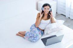Mujer en auriculares y con el ordenador portátil que trabaja en casa Fotografía de archivo libre de regalías