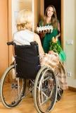 Mujer en ayudante de la reunión de la silla de ruedas Imagen de archivo