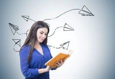 Mujer en azul que lee un libro, aviones de papel Fotografía de archivo libre de regalías
