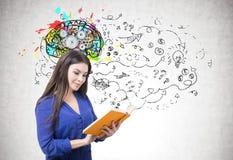 Mujer en azul que lee un libro, cerebro del diente Fotografía de archivo