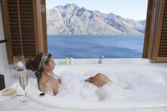 Mujer en bañera de la burbuja con el lago mountain fuera de la ventana Foto de archivo libre de regalías