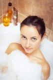 Mujer en bañera por completo de espuma Imagen de archivo libre de regalías