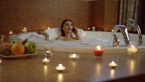 Mujer en baño que habla en el teléfono y que sostiene la tarjeta de banco metrajes