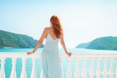 Mujer en balcón con paisaje marino tropical fotos de archivo