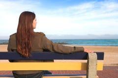 Mujer en banco al lado del mar Imagenes de archivo