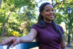 Mujer en banco de parque Fotos de archivo libres de regalías