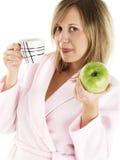 Mujer en bata de casa con café y la manzana Foto de archivo libre de regalías