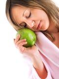 Mujer en bata de casa con la manzana Foto de archivo libre de regalías