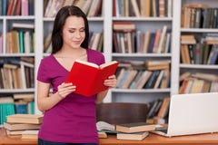 Mujer en biblioteca. Imagen de archivo libre de regalías