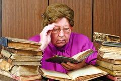 mujer en biblioteca con los libros religiosos Fotos de archivo libres de regalías